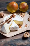 Camembert cheese with walnuts, honey and pears on rustic table Royalty Free Stock Images