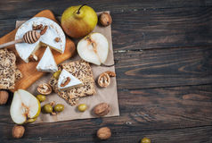 Camembert cheese with walnuts, honey and pears on rustic table. Glass of white wine Royalty Free Stock Photography