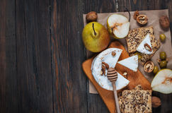 Camembert cheese with walnuts, honey and pears on rustic table. Glass of white wine Stock Photo