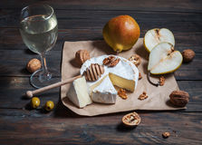 Camembert cheese with walnuts, honey and pears on rustic table. Glass of white wine Stock Photos