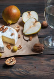 Camembert cheese with walnuts, honey and pears on rustic table. Glass of white wine Royalty Free Stock Photo