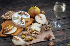 Camembert cheese with walnuts, honey and pears on rustic table. Glass of white wine Stock Images