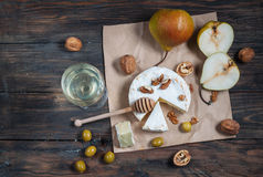 Camembert cheese with walnuts, honey and pears on rustic table. Glass of white wine Stock Image