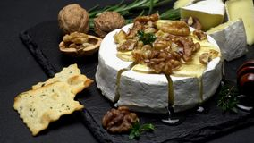 Camembert cheese and walnuts on stone serving board stock video footage