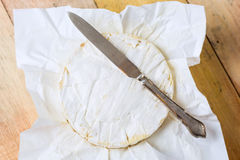 Camembert cheese wrapped in paper with vintage knife on wooden t Stock Images