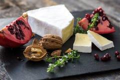 Camembert con i dadi ed il melograno Fotografia Stock