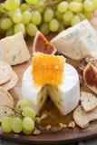 Camembert con la miel y la fruta, bocados en la bandeja de madera, vertical Imagenes de archivo