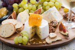 Camembert con la miel y la fruta, bocados en una bandeja de madera Imagen de archivo libre de regalías
