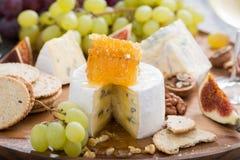Camembert con la miel y la fruta, bocados en una bandeja de madera Fotos de archivo