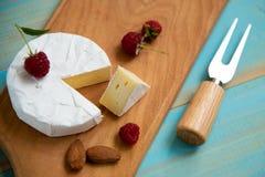 Camembert de fromage avec les framboises et les écrous, mélange sur le fond bleu photo libre de droits