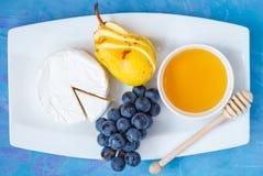 Camembert del brie del queso con la miel y las frutas en una placa blanca Foto de archivo