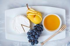 Camembert del brie del queso con la miel y las frutas en una placa blanca Imágenes de archivo libres de regalías