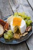 Camembert fresco com mel, uvas e biscoitos na placa Imagem de Stock