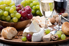Camembert, fresh baguette, grapes and wine on a wooden tray Stock Images