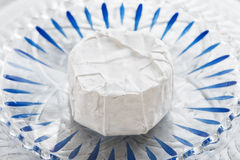 Camembert on glass plate. Camembert cheese on glass plate with blue stripes Royalty Free Stock Image
