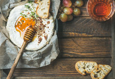 Camembert , grapes, baguette slices and glass of rose wine Stock Image
