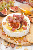 Camembert with grapes, figs, honey, crackers and walnuts Royalty Free Stock Images