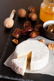 Camembert with honey, dates and nuts on dark background. Vertical, close-up Royalty Free Stock Image