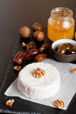 Camembert with honey, dates and nuts on dark background. Vertical, close-up Stock Photo