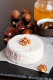 Camembert with honey, dates and nuts on dark background. Vertical, close-up Stock Images