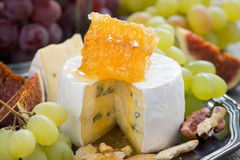 Camembert with honey and fruit, snack on a plate, close-up Stock Image