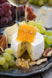 Camembert with honey and fruit, snacks and wine on a plate Stock Photos