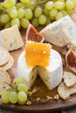 Camembert with honey and fruit, snacks on wooden tray, vertical Stock Images
