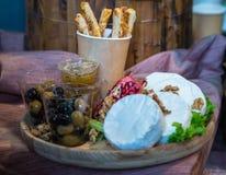 Camembert mit Nüssen und Oliven Stockfotografie