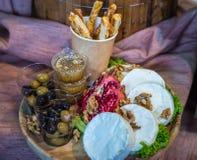 Camembert mit Nüssen und Oliven Stockfoto