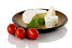 Camembert op een ceramische die schotel en een tomaat op witte achtergrond wordt geïsoleerd Royalty-vrije Stock Foto