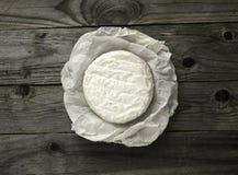 Camembert ou brie savoureux mûr de fromage enveloppé dans un papier sur un vieux Image libre de droits