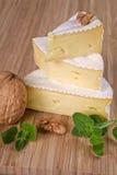 Camembert pieces. Cut camembert pieces arranged on wooden board stock photos