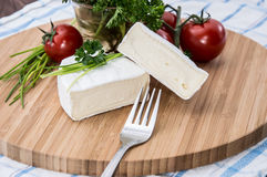 Camembert pieces on cutting board Royalty Free Stock Photo