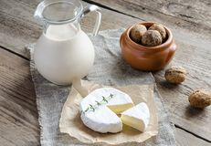 Camembert with pitcher of milk and whole nuts. On the wooden table Royalty Free Stock Photos