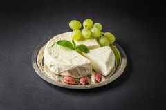 Camembert on the Plate with Grape, Peanuts and Mint.  Royalty Free Stock Photography