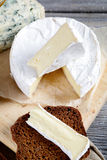 Camembert, roquefort and rye bread slice on a cutting board Royalty Free Stock Photos