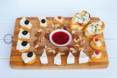 Camembert ser, oliwki, krakersy, dokrętki, dżem, cranberries i Błękitnego sera plasterek na opiekacza chlebie na tnącej desce i, fotografia stock