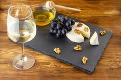 Camembert sera, dokrętek, miodu i cukierki winogrona na tle szkło biały suchy wino, obrazy stock