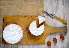 Camembert sur une planche à découper en bois Photographie stock