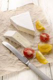 Camembert and tomato on paper Royalty Free Stock Images