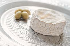 Camembert on tray with olives. Camembert on a silver tray with green olives Royalty Free Stock Photo