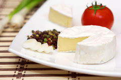 Camembert with vegetables. Camembert cheese on white plate with vegetables Royalty Free Stock Images