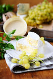 Camembert on white plate and grapes Royalty Free Stock Image