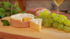 Camembert with white wine, grapes and bread. Circular movement of the camera around a piece of Camembert on a wooden board. Against the background of wine stock footage