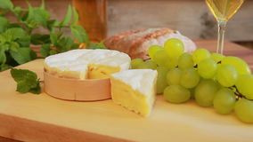 Camembert with white wine, grapes and bread. Circular movement of the camera around a piece of Camembert on a wooden board. Against the background of wine stock video
