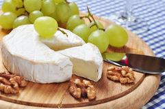 Camembert. On wooden cutting board with grape and walnut closeup Stock Photos