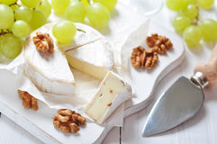 Camembert. On wooden cutting board with grape and walnut closeup Royalty Free Stock Photo