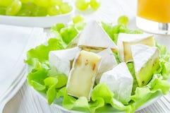 Camembertk?se, gr?ne Trauben und Glas Orangensaft auf wei?em Holztisch gesundes Fr?hst?ckskonzept lizenzfreie stockfotografie