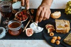Camembertost med fikonträd och muttrar i händer i köket På träskärbräda Slut upp sikten, ingredienser för sunt royaltyfri bild