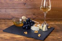 Camembertost, muttrar, honung och söta druvor på bakgrunden av ett exponeringsglas av vitt torrt vin royaltyfri foto